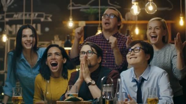 Diverse Gruppe von Freunden schaut tv in der Sporstbar. Schöne junge Leute trinken, viel Spaß und jubeln für ihr Team.