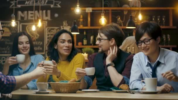 Přátelé mají zábavu v Cafe, pít horké nápoje, mluví a sdílení. Krásných mladých lidí ve stylovém prostředí