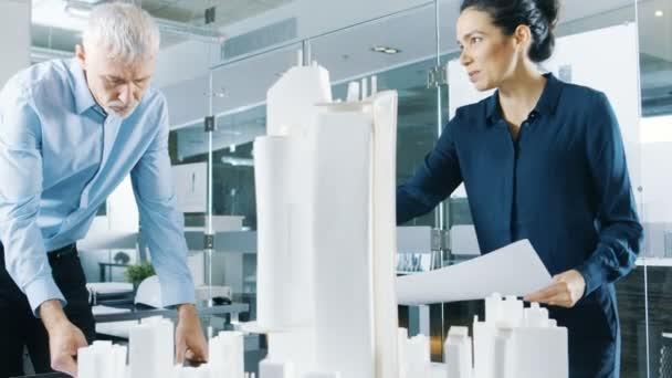 Dvě profesionální samec a samice architektonické techniky práce s plány a na návrh modelu budovy pro projekt urbanistické plánování.