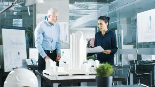 In the Architectural Bureau Female Engineer Brings Blueprints and Shows them to Senior Architect, They Discuss Project. They Work as Urban Planners on a Building Model.