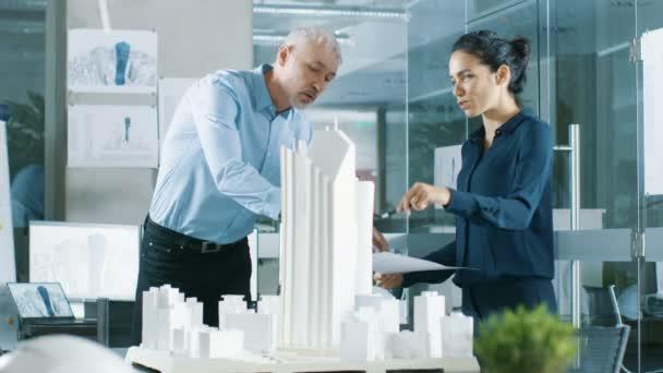 Zwei professionelle männliche und weibliche Architektur Ingenieure arbeiten mit Blaupausen und auf ein Gebäude-Modell-Design für das städtebauliche Projekt. Reinigen Sie minimalistisch Office Betonwände bedeckt von Blaupausen und Dokumente