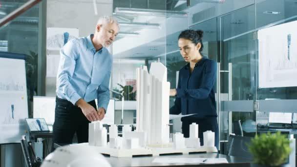 Dva profesionální samec a samice architektonické techniky práce s plány a na návrh modelu budovy pro městské plánování Project.Clean minimalistický úřadu, betonové zdi plány a dokumenty.