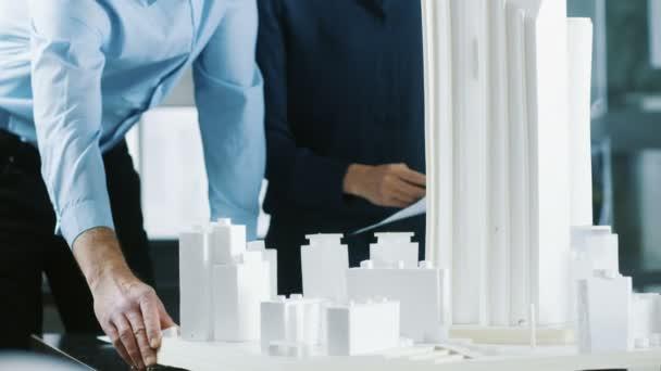 männliche Oberingenieurin und weibliche Architekturdesignerin arbeiten an einem Baumodell für das städtebauliche Projekt.