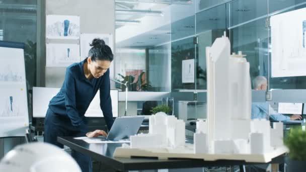 Ženské architektonické Designer funguje na notebooku, inženýrství nového modelu budovy pro městské plánování projektu. Čistý minimalistický úřadu, betonové zdi plány a dokumenty.