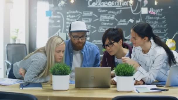 Rozmanitý tým mladých vývojářů mají setkání týmu pomocí přenosného počítače. Krásné mladé lidi ve světlé moderní kancelářské prostředí