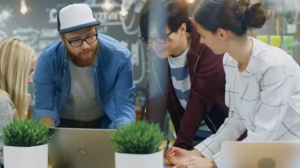 Rozmanité tým talentovaných mladých vývojáři mají brainstormingu. Mají diskuse, použijte Laptop a nahlížet do dokumentů. Stylový lidé pracují v moderním prostředí.