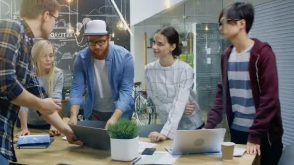 Vedoucí týmu ukazuje notebook ke skupině talentovaných mladých vývojářů, začnou diskusi na jednací stůl. Kreativní lidé ve stylovém prostředí.