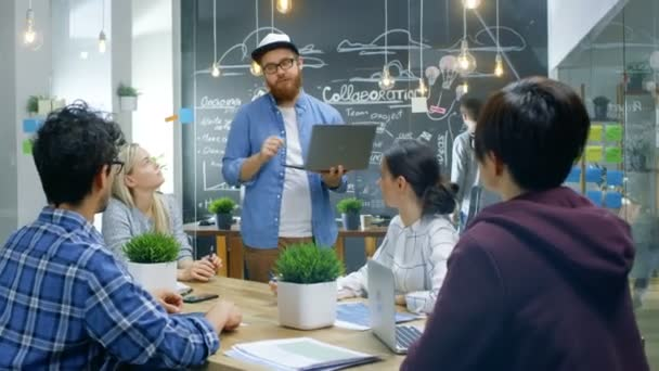 Vedoucí projektu Kreativní drží Laptop a rozhovory na setkání týmu talentovaných mladých vývojářů diskutují, cíle, cíle a ambice. Stylový obchodní kancelář
