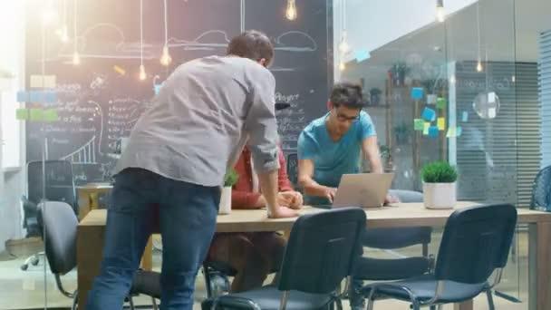 Zeitraffer des geschäftigen Kreativbüros, in dem stilvolle junge Leute an PCs arbeiten, Besprechungen und Diskussionen führen.
