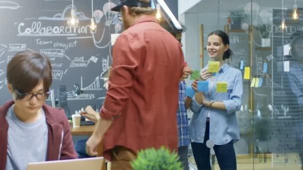 Riskantní práce úřadu, kde mladí kreativní lidé pracují na laptopy, osobní počítače a osnovy plánu projektu s Lepící papíry na skleněnou stěnu.