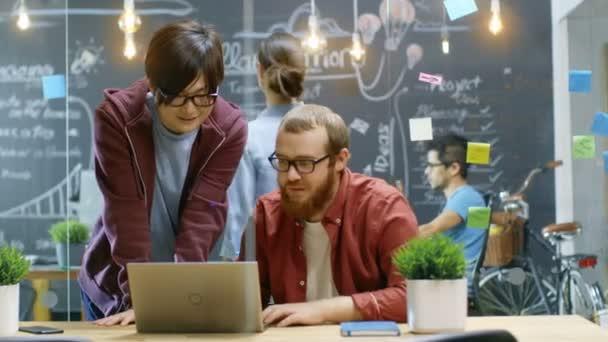 Due Creative designer guardare il Laptop e hanno grande successo, che fanno High Five e ridere. In ufficio con persone di talento lavoro elegante sfondo