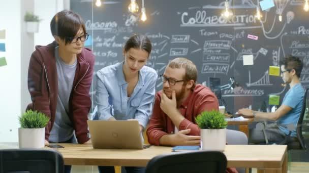 Tři kreativní lidé mají aktivní diskuse o probíhajícím projektu při používání notebooku. Stylový mladých lidí práci v moderní prostředí.