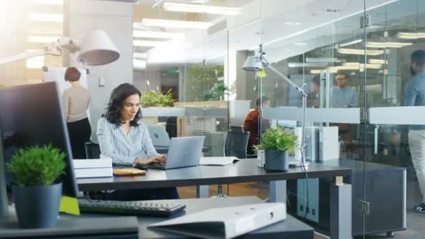 Busy International Office, Beautiful Hispanic Woman Working at Her Desk on a Laptop, She Waves Hello to the Passing Colleague, in the Background Her Coworkers Have Work Related Conversations. Stylish Office with Bright Young People.