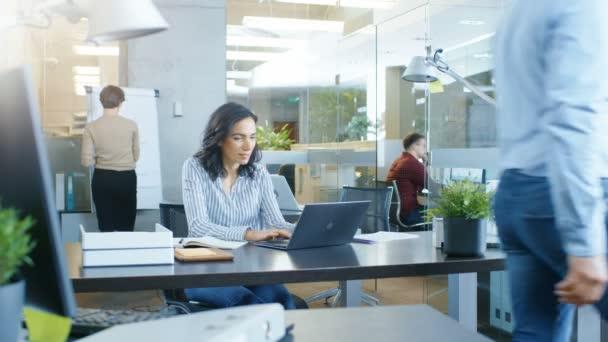 Zaneprázdněnost mezinárodního úřadu, krásná hispánský žena pracující u svého stolu v přenosném počítači, ona vlny Hello předávání kolegovi, v pozadí její spolupracovníci mají práce související konverzace. Stylová kancelář s schopných mladých lidí.