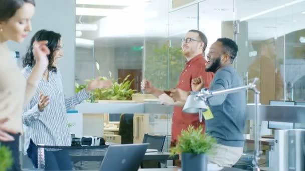 Různorodá skupina mladých žen a mužů tančit a bavit se v moderní kanceláři.