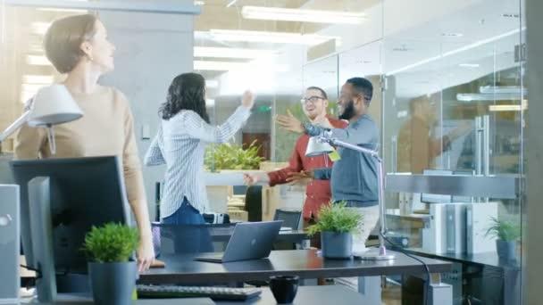 Různorodá skupina mladých žen a mužů tančit a bavit se v moderní kanceláři. Firemní večírek.