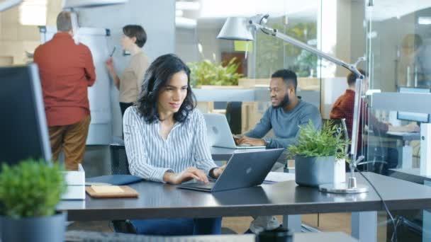 Zaneprázdněnost mezinárodního úřadu, krásné hispánské žena pracující na její stůl na Laptop, ona píše dole informace v její poznámkového bloku. V pozadí její spolupracovníci.