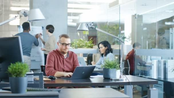 Rušné mezinárodní podnikové, kavkazské muži, kteří pracují u stolu v přenosném počítači. V pozadí kreativní mladí lidé pracovní.