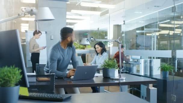 Rušné hlavní kanceláři, muži, kteří pracují na notebooku značky významný kontrakt a skoky na oslavu, dává dost jeho spolupracovníky. Každý je šťastný.