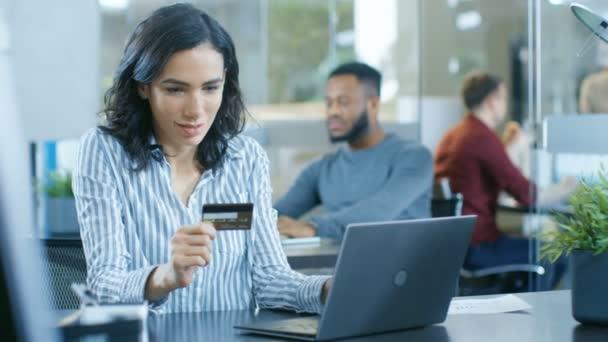Krásné ženské úřednice dělá Internet nákup z její Laptop kreditní kartou. V pozadí kreativní mladí lidé pracovní.