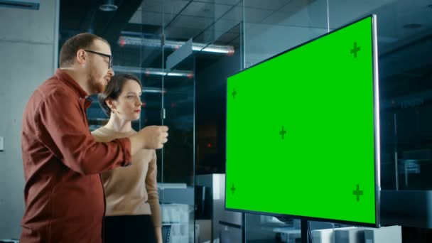 Late at Night Male and Female Specialists in Conference Room Have Discussion about Mock-up Chroma Key Green Screen TV.