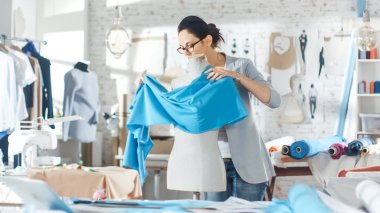 Beautiful Female fashion, designer,  Adjusting Fabrics on a Tailored Mannequin. In Her Studio Various Sewing Items and Colorful Fabrics Laying around, Mannequins Standing, and Sketches Pinned.