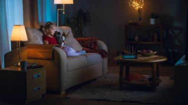 In the Evening Little Girl and Her Mom Sit on a Couch in a Living Room. Girl Holds Her Soft Toy and Watches TV.