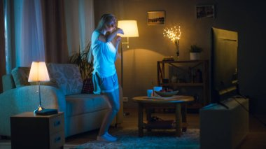 In the Evening Beautiful Woman Happily Dances in Her Living Room while Watching TV, Also She Holds Smartphone.