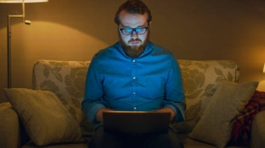 Portrait Shot of a Man Sitting on a Couch in His Living Room, Laptop on His Knees. He's Working. Floor Lamps are Turned On.