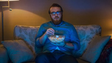 Portrait Shot of a Man Sitting on a Sofa in His Living Room, Eating Popcorn and Watching TV. Floor Lamps are Turned ON.