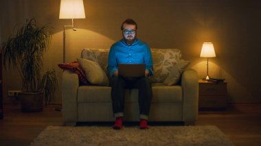 Portrait Shot of a Man Sitting on a Couch in His Living Room, Laptop on His Knees. He's Working. He Looks Straight at the Camera. Floor Lamps are Turned On.