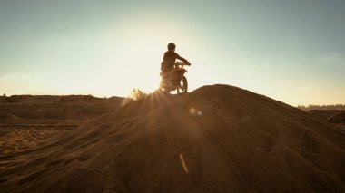 Professional Motocross Rider on FMX Motorcycle Drives on the Sand Dune and Stops There to Admire Scenic Sunsetting View.