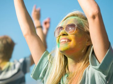 Portrait of a Beautiful Blonde Girl Dances in Celebration of Holi Festival With Her Friends. Her Face and Clothes are Covered with Colorful Powder. People Dancing in the Background.