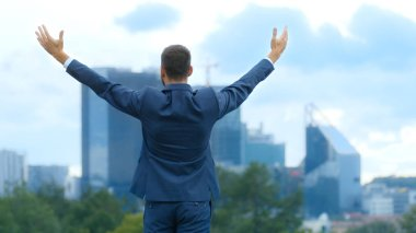 Happy Successful Business Man Raises His Hands, He Has His Business Victory. In The Background Big City with Skyscrapers.