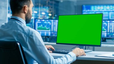 Stock Market Trader Working on a Computer with Isolated Mock-up Green Screen. In the Background Monitors Show Stock Ticker Numbers and Graphs.