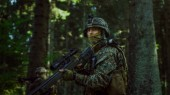 Fully Equipped Sniper Soldier Wearing Camouflage Uniform Attacking Enemy, Rifle in Firing Position. Military Operation in Action, Squad Running in Formation Through Dense Forest. Side View Long Shot.