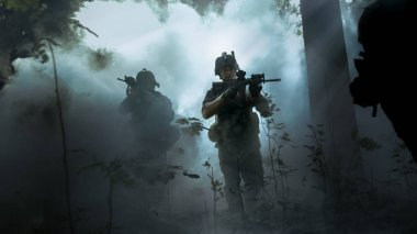Fully Equipped Soldiers Wearing Camouflage Uniform Attacking Enemy, Rifles Ready to Shoot. Military Operation in Action, Squad Running in Formation Through Cold Dense Smokey Forest.