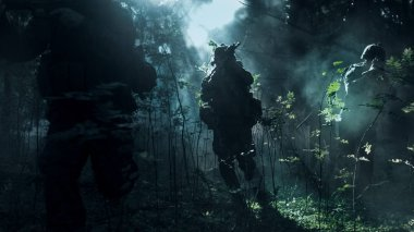 Fully Equipped Soldiers Wearing Camouflage Uniform Attacking Enemy, Rifles Ready to Shoot. Military Operation in Action, Squad Running in Formation Through Cold Dark Dense Smokey Forest.