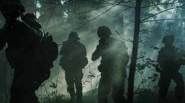 Squad of Five Fully Equipped Soldiers in Camouflage on a Reconnaissance Military Mission, Rifles Ready to Shoot. They're Moving in Formation Through Dense Smokey Forest.
