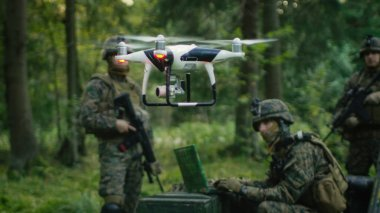 In the Military Staging Base Army Engineer and Soldiers Fly Military Grade Industrial Drone for their Reconnaisance/ Surveillance Mission/ Operation. Theater of Operation is in Forest Area.