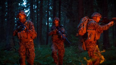 Squad of Five Fully Equipped Soldiers in Camouflage on a Reconnaissance Military Night Mission. They're Lit by Red Flare and Move Through Dense Forest.