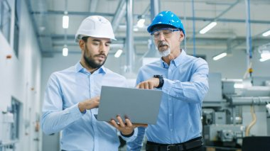 Head of the Project Holds Laptop and  Discusses Product Details with Chief Engineer while They Walk Through Modern Factory.