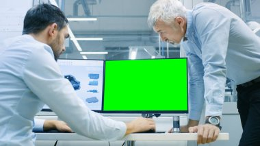 Industrial Designer Has Conversation with Senior Engineer While Working in CAD Program, One Has a Green Screen Chroma Key Template Great for Mockup. He Works on Personal Computer with Two Monitors.