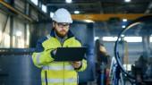 Fotografie Industrial Engineer v přilbu nosit bezpečnostní vestu používá notebook. Pracuje v továrně vyrábějící těžkého průmyslu s různými obráběcí procesy jsou v průběhu