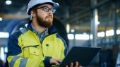 Industrial Engineer v přilbu nosit bezpečnostní vestu používá notebook. Pracuje v továrně vyrábějící těžkého průmyslu s různými obráběcí procesy jsou v průběhu