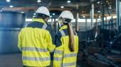 Rückansicht Schuss der männlichen und weiblichen Wirtschaftsingenieure mit Diskussion und Nutzung Laptop bei einem Spaziergang durch Schwerindustrie Manufacturing Factory. Sie tragen hart Hüte und Sicherheitswesten.