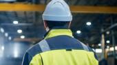Fotografie Průmyslový inženýr v přilbu a bezpečnostní vestu rozhlíží do velkých těžkého průmyslu výrobního závodu