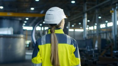 Shot of Female Industrial Worker in the Hard Hat Walking Through Heavy Industry Manufacturing Factory. In the Background Various Metalwork Project Parts Lying