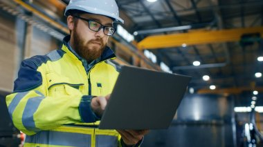 Industrial Engineer in Hard Hat Wearing Safety Jacket Uses Touchscreen Laptop. He Works at the Heavy Industry Manufacturing Factory.