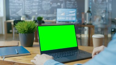 Male Office Worker at His Desk Works on a Laptop with Mock-up Green Screen. Over the Shoulder Close-up Footage. In the Background Creative Office.